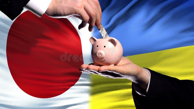 Inversión de Japón en Ucrania, mano que pone el dinero en piggybank en fondo de la bandera imágenes de archivo libres de regalías