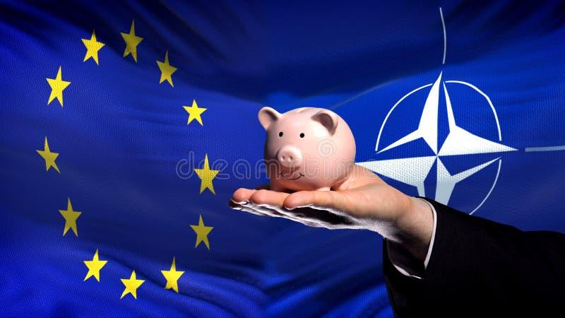Inversión de la UE en OTAN, mano del hombre de negocios que lleva a cabo el piggybank en fondo de la bandera imagen de archivo