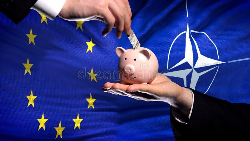 Inversión de la UE en OTAN, mano que pone el dinero en piggybank en fondo de la bandera fotografía de archivo libre de regalías