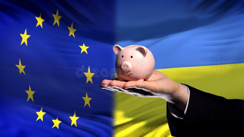 Inversión de la UE en Ucrania, mano del hombre de negocios que lleva a cabo el piggybank en fondo de la bandera foto de archivo libre de regalías