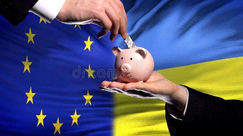Inversión de la UE en Ucrania, mano que pone el dinero en piggybank en fondo de la bandera fotos de archivo libres de regalías