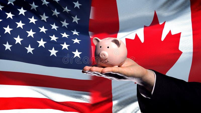 Inversión de los E.E.U.U. en Canadá, mano del hombre de negocios que lleva a cabo el piggybank en fondo de la bandera fotografía de archivo