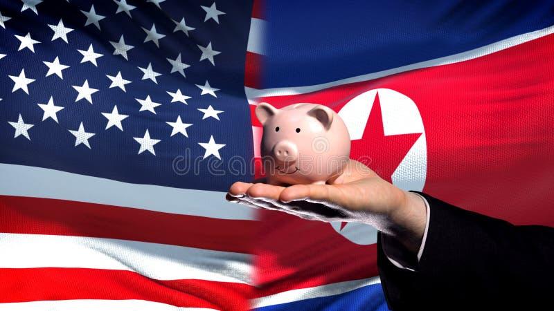 Inversión de los E.E.U.U. en Corea del Norte, mano del hombre de negocios que lleva a cabo el fondo de la bandera del piggybank imágenes de archivo libres de regalías