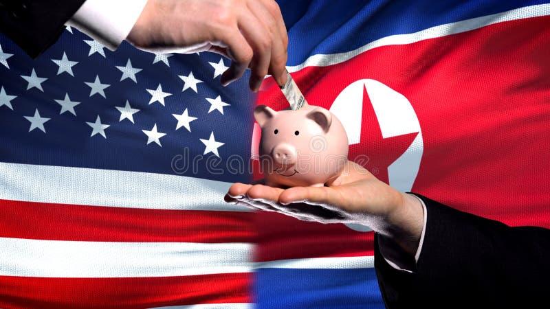 Inversión de los E.E.U.U. en Corea del Norte, mano que pone el dinero en piggybank en fondo de la bandera foto de archivo libre de regalías