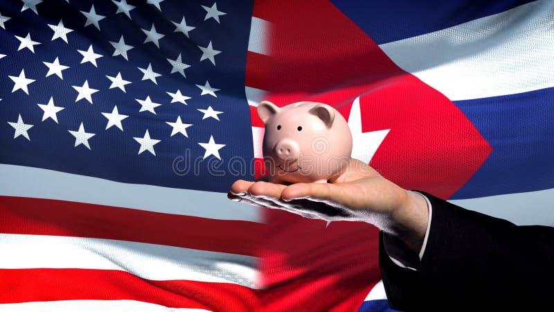 Inversión de los E.E.U.U. en Cuba, mano del hombre de negocios que lleva a cabo el piggybank en fondo de la bandera imagen de archivo