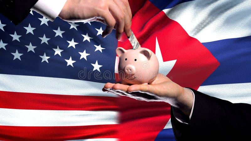 Inversión de los E.E.U.U. en Cuba, mano que pone el dinero en piggybank en fondo de la bandera imagenes de archivo