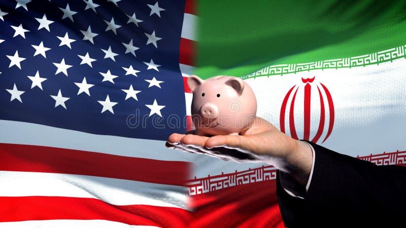 Inversión de los E.E.U.U. en Irán, mano del hombre de negocios que lleva a cabo el piggybank en fondo de la bandera imagen de archivo libre de regalías