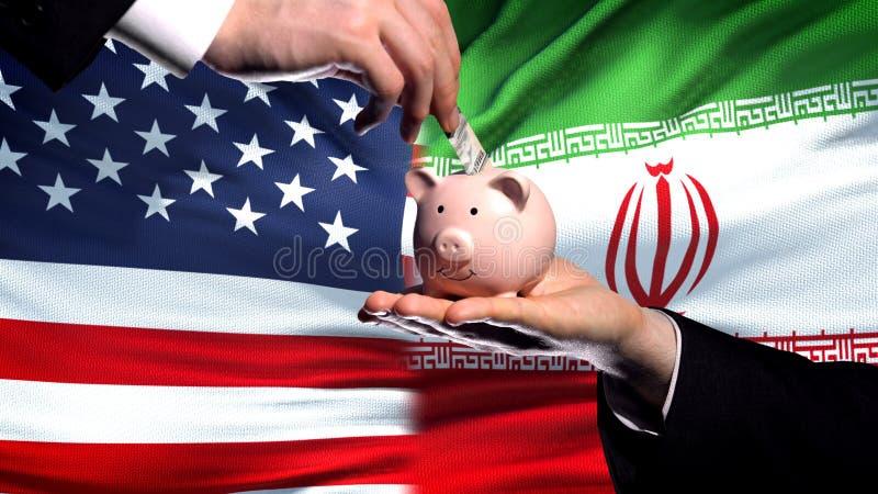 Inversión de los E.E.U.U. en Irán, mano que pone el dinero en piggybank en fondo de la bandera fotos de archivo libres de regalías
