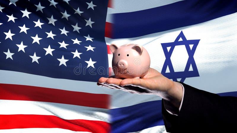 Inversión de los E.E.U.U. en Israel, mano del hombre de negocios que lleva a cabo el piggybank en fondo de la bandera imágenes de archivo libres de regalías