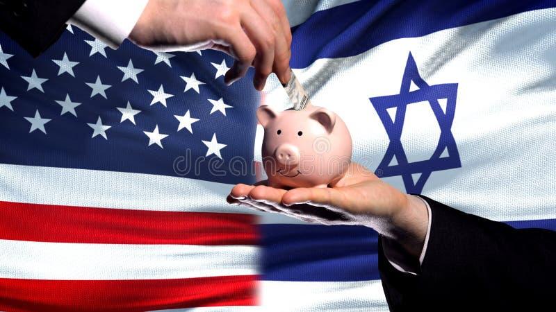 Inversión de los E.E.U.U. en Israel, mano que pone el dinero en piggybank en fondo de la bandera foto de archivo libre de regalías