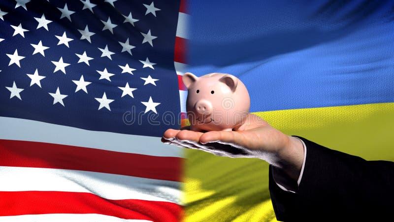 Inversión de los E.E.U.U. en Ucrania, mano del hombre de negocios que lleva a cabo el piggybank en fondo de la bandera fotografía de archivo