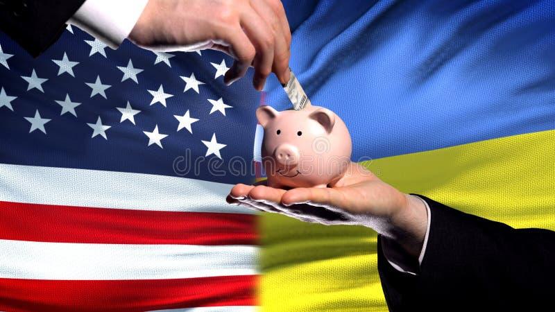 Inversión de los E.E.U.U. en Ucrania, mano que pone el dinero en piggybank en fondo de la bandera imagen de archivo libre de regalías