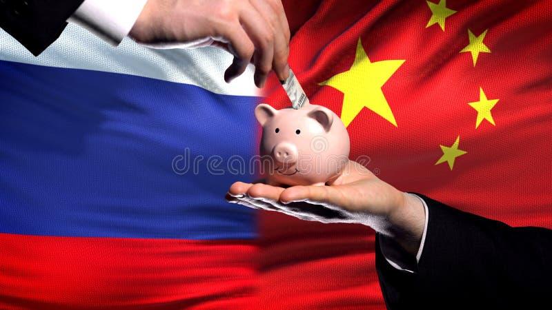 Inversión de Rusia en China, mano que pone el dinero en piggybank en fondo de la bandera imágenes de archivo libres de regalías