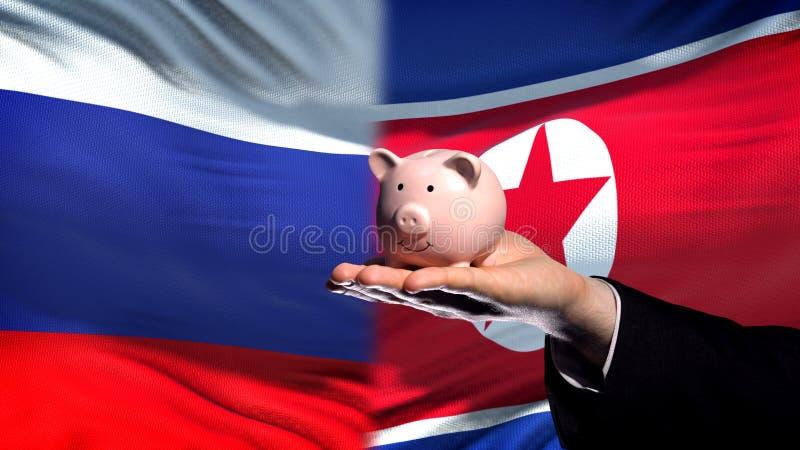 Inversión de Rusia en Corea del Norte, mano que lleva a cabo el piggybank en fondo de la bandera imagen de archivo