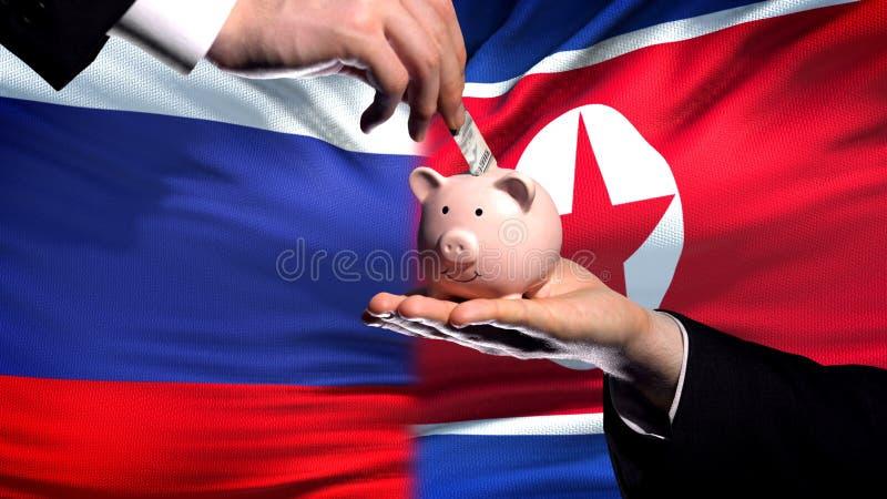 Inversión de Rusia en la mano de Corea del Norte que pone el dinero en fondo de la bandera del piggybank fotos de archivo