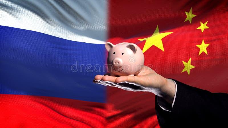 Inversión de Rusia en la mano del hombre de negocios de China que lleva a cabo el piggybank en fondo de la bandera fotografía de archivo