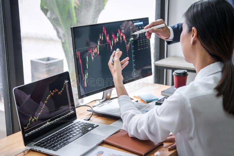 Inversión que trabaja con el ordenador, planeamiento del equipo del negocio y analizando el comercio del mercado de acción del gr imagen de archivo