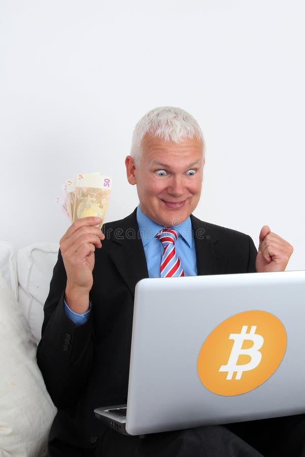 Inversor del banquero de Bitcoin feliz con el ordenador portátil y el dinero imagen de archivo