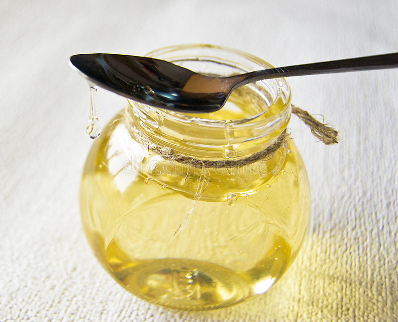Invert syrup. In a glass container, honey in a glass jar royalty free stock photos