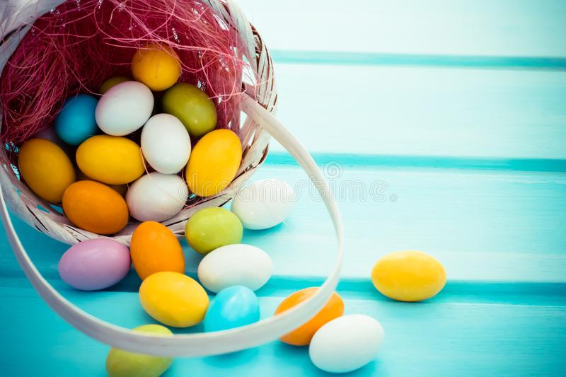 Inverted basket with easter sweet colorful chocolate eggs and pink hay. Copyspace. Inverted basket with easter sweet colorful small chocolate eggs and pink hay royalty free stock photography