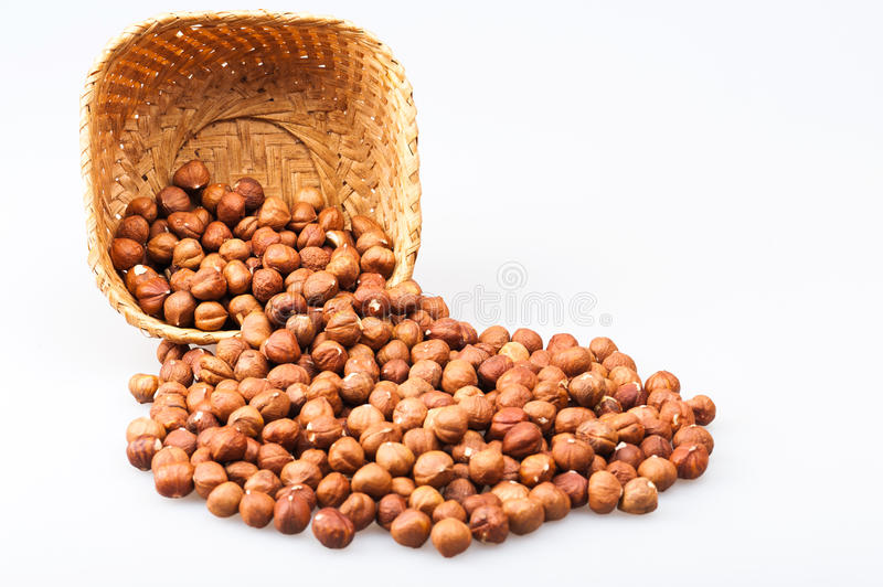 Inverted basket with hazelnuts. Poured out of the basket hazelnuts isolated on white background royalty free stock photos