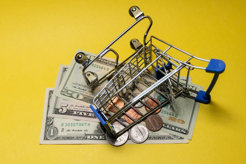 An inverted metal shopping trolley lies on small US bills and coins. The concept of online purchases and sales, unsuccessful. An inverted metal shopping trolley stock photography