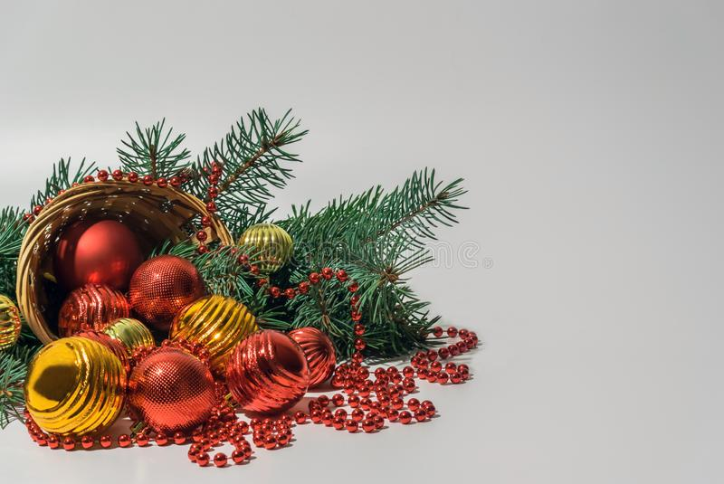 Inverted wicker basket with toys of red and gold color to decorate the Christmas tree on a light background. Composition of an inverted wicker basket with toys royalty free stock image