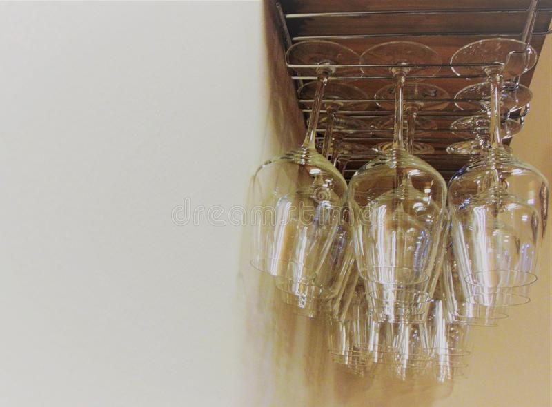 Inverterade vinexponeringsglas på en bakgrund av den ljusa beigea väggen tonat foto royaltyfri foto