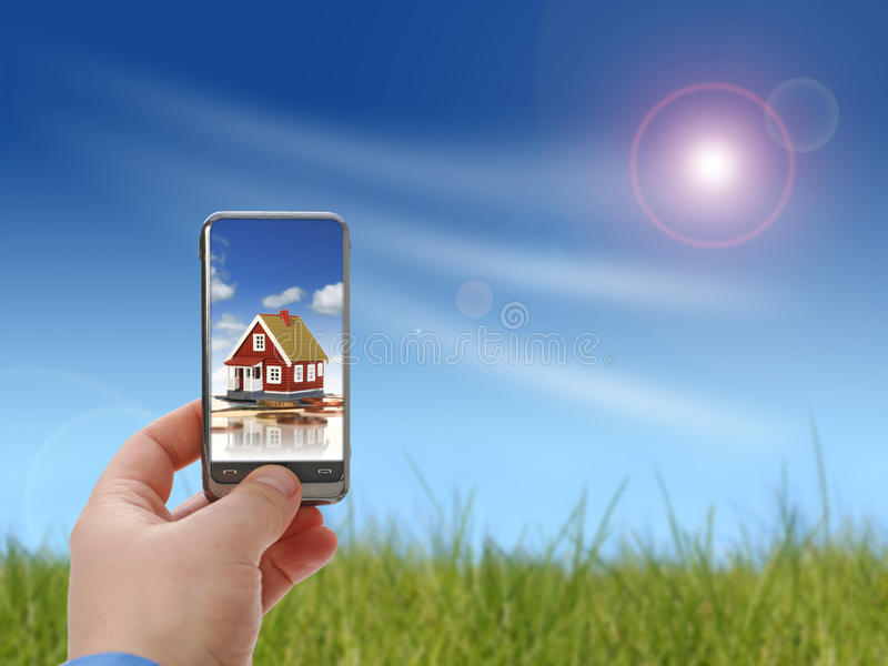 Invest in real estate. Mobile phone in hand over sky background. Real estate concept royalty free stock image