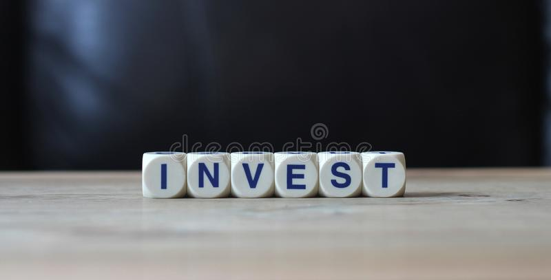 Invest. White letter cubes on table and black background word invest wisely stock photography