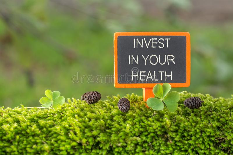 Invest in your health text on small blackboard. Sign on green moss with Clover , blur green tree plant background royalty free stock photography