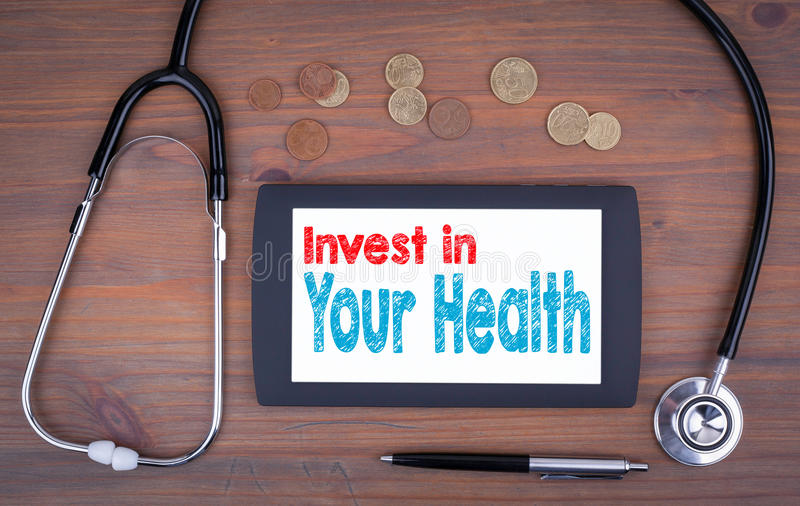 Invest in your health. Text on tablet device. On a wooden table stock image