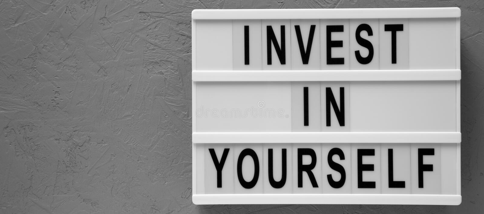 `Invest in yourself` words on a lightbox over gray background, top view. Overhead, flat lay, from above. Space for text stock photos