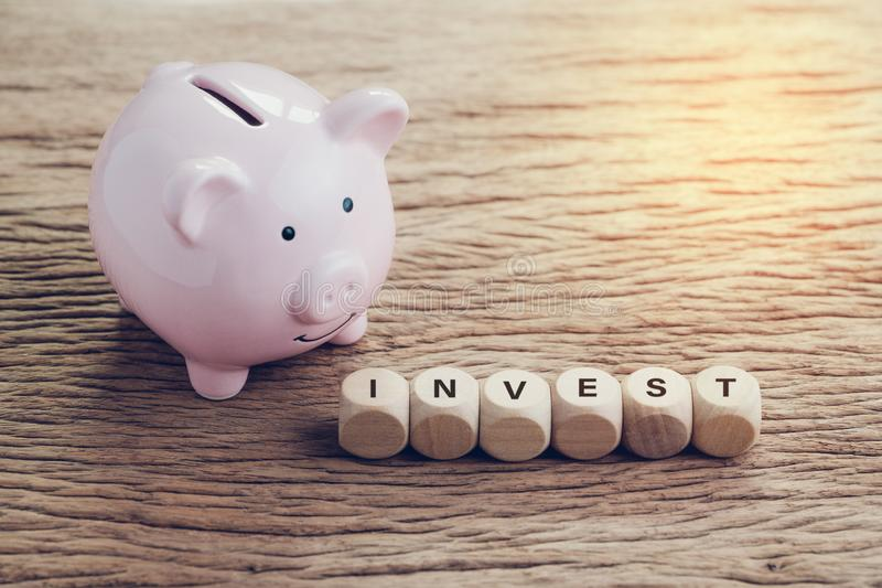 Investeringen finans, bankrörelset, sparande pengarbegrepp, den rosa spargrisen med träkuben med alfabet som bygger ordet, INVEST royaltyfri bild