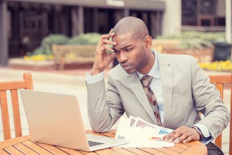 Investeringkonsulent för upptagen man som analyserar för rapportbalansräkning för företag finansiellt meddelande arkivfoto