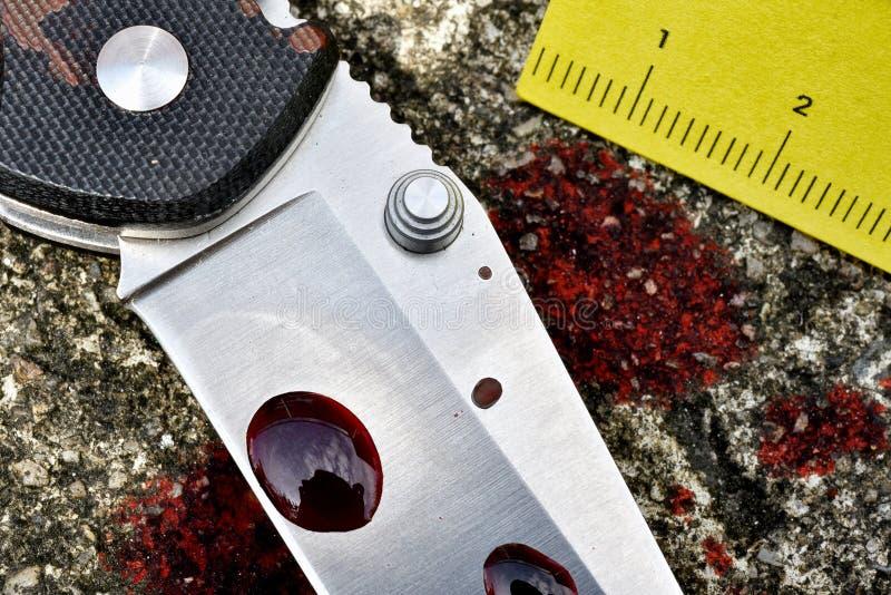 Investigación de la escena del crimen, cuchillo sangriento con los marcadores criminales en la tierra, pruebas del homicidio imágenes de archivo libres de regalías