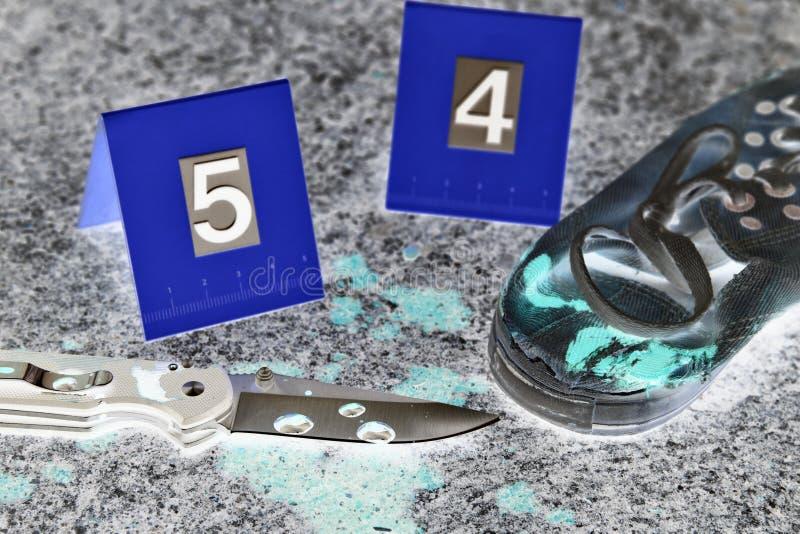 Investigación de la escena del crimen, cuchillo sangriento y zapatos del ` s de la víctima con los marcadores criminales en la ti imagen de archivo libre de regalías