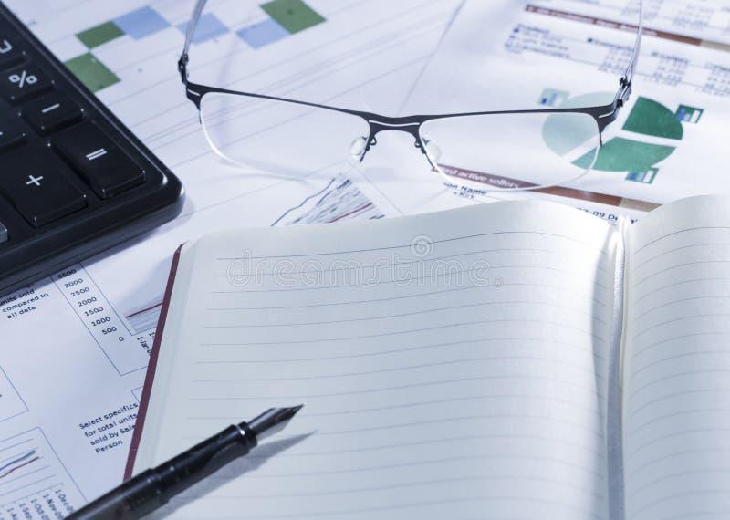 Investigación empresarial Cuaderno con la pluma, la calculadora, los vidrios en informes y el papel con las figuras, cartas imágenes de archivo libres de regalías