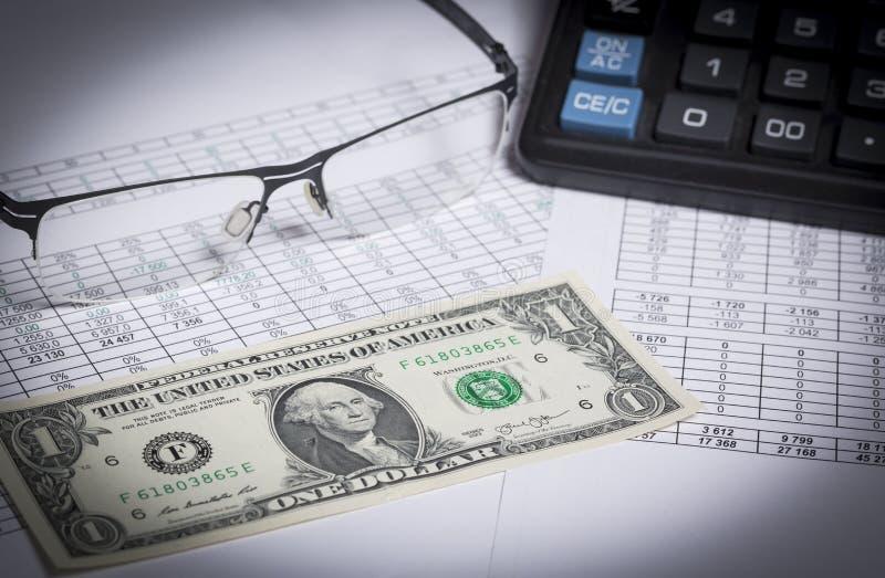 Investigación empresarial Primer de gafas, billete de dólar, calculadora en el papel con los dígitos foto de archivo libre de regalías