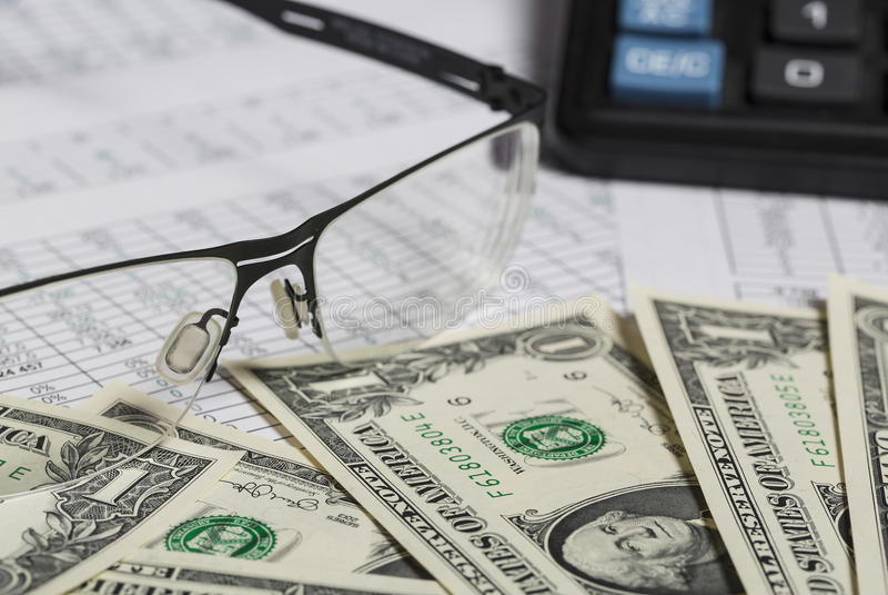 Investigación empresarial Primer de las gafas, billetes de dólar, calculadora en el papel con los dígitos fotografía de archivo