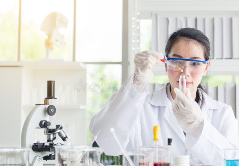Investigación hermosa de la mujer del científico y muestra médica de las sustancias químicas del descenso en tubo de ensayo en el fotos de archivo libres de regalías