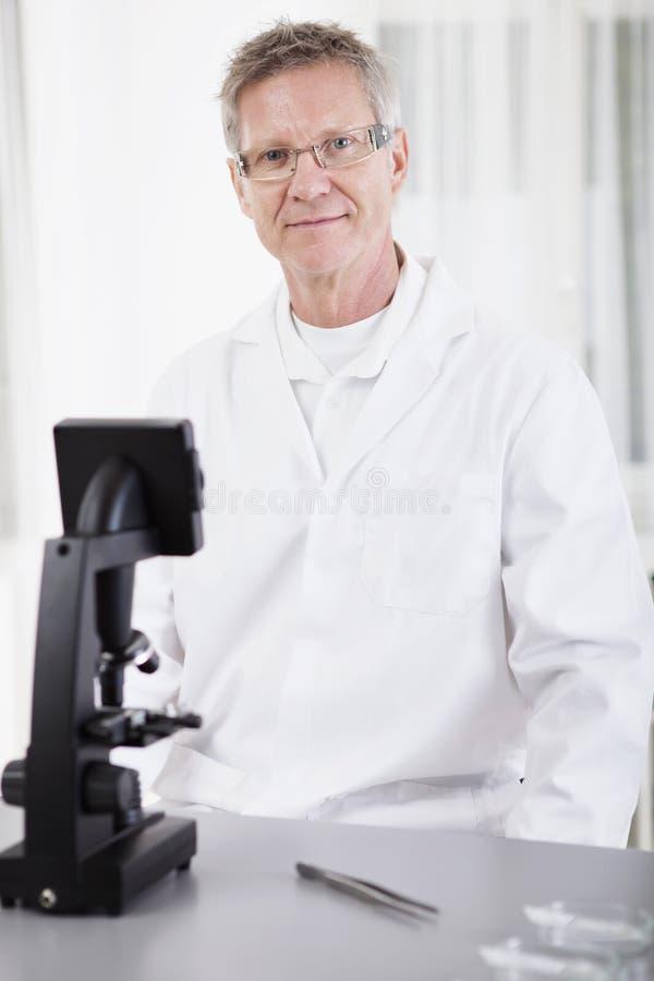 Investigador científico con el microscopio fotos de archivo