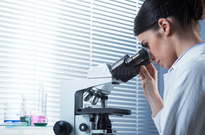 Investigador de sexo femenino que usa el microscopio fotografía de archivo libre de regalías