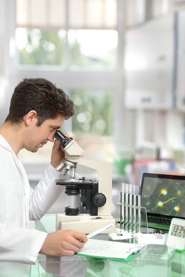 Investigador de sexo masculino con el microscopio en centro de investigación moderno imagen de archivo libre de regalías