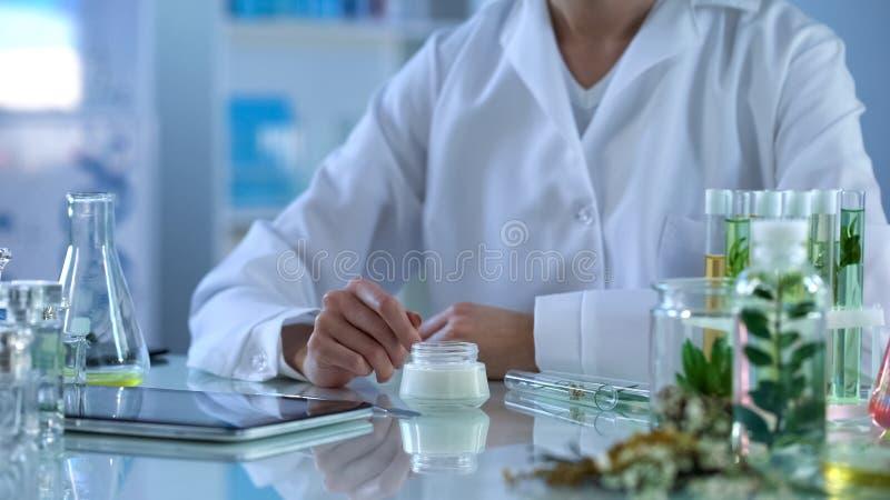 Investigador del laboratorio de la cosmetología que prueba la nueva crema orgánica, tableta moderna en la tabla imagen de archivo