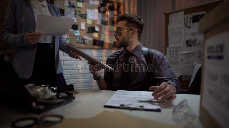 Investigador federal que mira a través de ficheros, caso complicado, pistas de la oficina imagenes de archivo