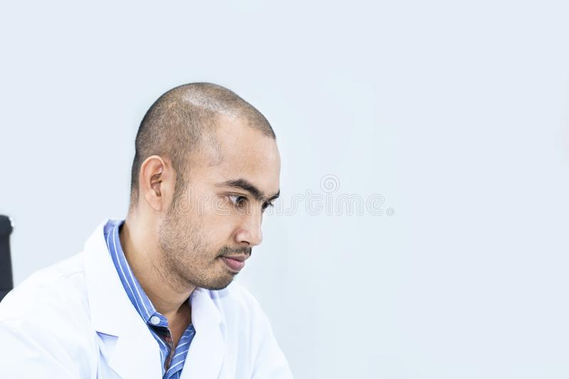 Investigador hermoso mayor que piensa en sueño Doctor en la habitación blanca foto de archivo libre de regalías