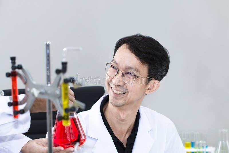 Investigador hermoso y sonriente mayor que habla con el científico imagenes de archivo