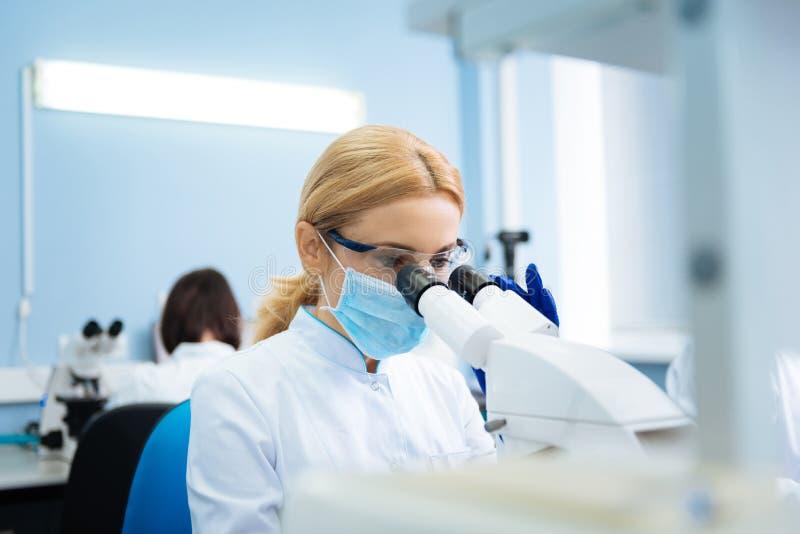 Investigador joven serio que mira en el microscopio en el laboratorio imagenes de archivo