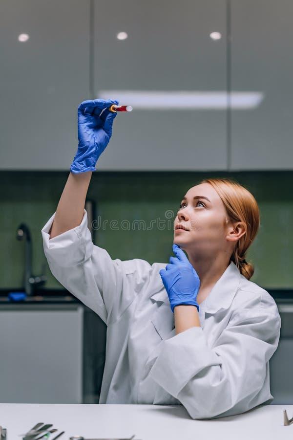 Investigador m?dico o cient?fico de sexo femenino que mira un tubo de ensayo en un laboratorio imagen de archivo
